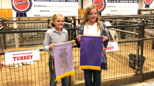Caroline Scarlett and Laura Jessup holding champion banners